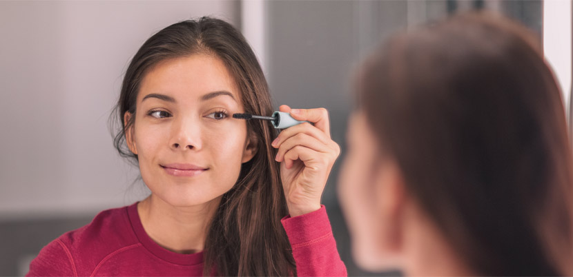 woman putting on mascara in mirror